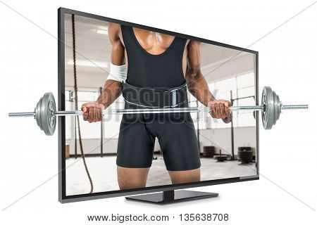 Mid-section of bodybuilder lifting heavy barbell weights against exercise ropes hanging and equipment
