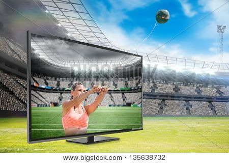 Portrait of sportswoman practising hammer throw against rugby stadium