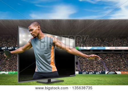 Front view of sportsman practising discus throw against american football arena