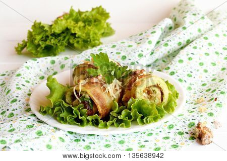 Fried zucchini rolls with grated cheese, fresh chopped parsley and crushed walnuts. Home zucchini rolls arranged on a green lettuce and on a plate. Vegetable appetizer. Closeup