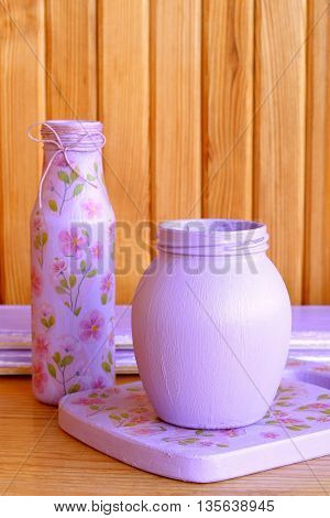 Colored glass bottle and cutting board. Handmade decoupage bottle with flower pattern. Art and craft idea to create kitchen decor. Cottage chic kitchen decoration. Wooden background