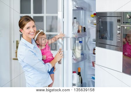 Happy woman opening refrigerator while carrying baby girl at home