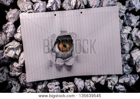 Hand holding environmental light bulb against lined paper notebook on crumpled paper