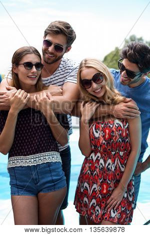 Happy men embracing women near pool on a sunny day