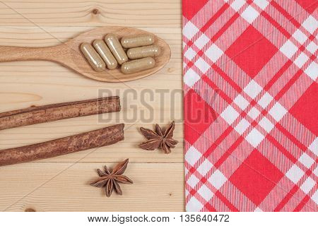 Herbal capsules on wooden spoon. herb for healthy living.