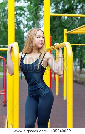 Young sports fitness model doing the exercises, the crossfit and posing on the playground on the horizontal bar and parallel bars, the stairs.