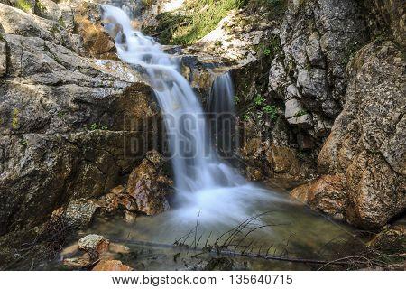Flowing waterfall over limestone rocks in the Carpathians