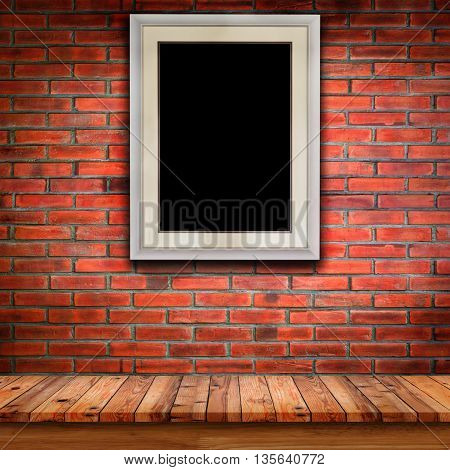 Empty wood table and black photo frame on brick wall background