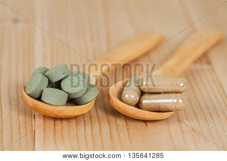 Herbal pill on wooden spoon. herb for healthy living.