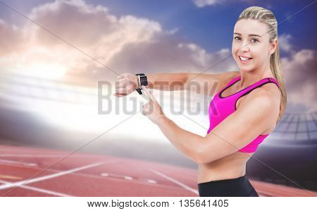 Female athlete using her smart watch against race track