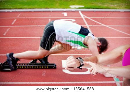 Female athlete using her smart watch against athletic man on the starting line putting his foot in the starting block