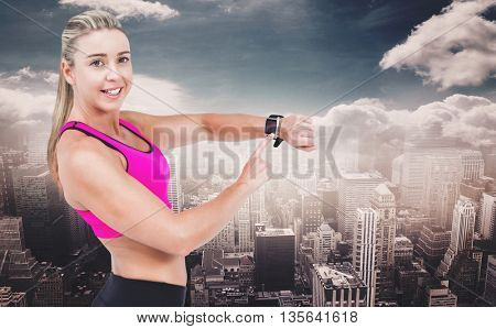 Female athlete using her smart watch against aerial view of a city on a cloudy day
