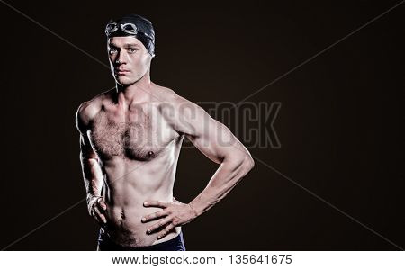 Swimmer standing with hand on hip against grey vignette