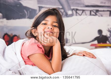 Pretty indian child lying down on white bed with hands on chin. Cute asian smiling little girl in her bed. Happy child relaxing at bed and looking camera.