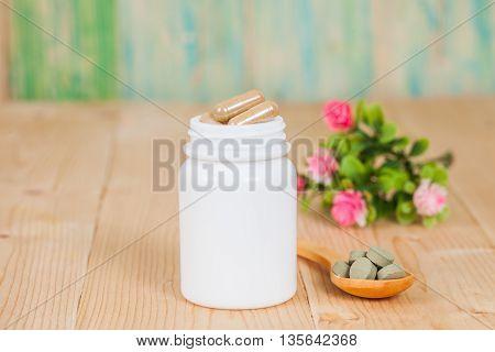 herb capsules spilling on a white bottle