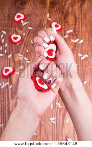 Hearts in hands of the person on a table
