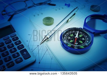 Compass pen glasses and coin on notebook business vision concept