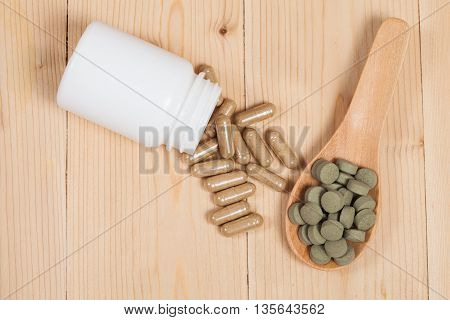 herb capsules spilling out of a bottle and herb pill