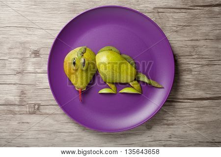 Lizard made of fresh fruits on plate and wood