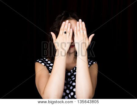 Close-up woman looks straight into the camera on a black background. laughing woman covering her eyes with her hands. expresses different emotions.