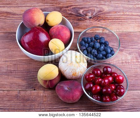 Fruit and berries in plates and on a table on a table