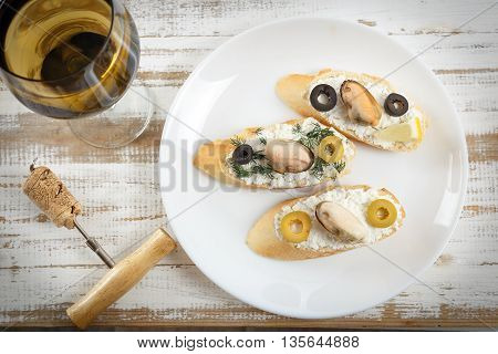 Tasty various italian sandwiches with seafood against rustic wooden background. Crostini with cheese mussels and sliced olives on white plate with glass of wine horizontal top view