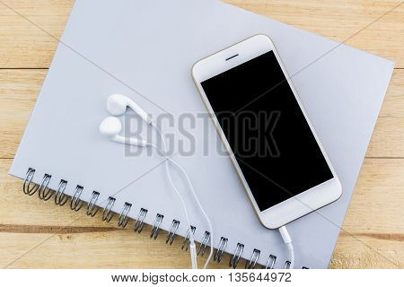Close up of mobile phone Smart phone on the spiral notebook.