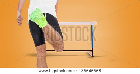 Rear view of male athlete running on isolated orange background