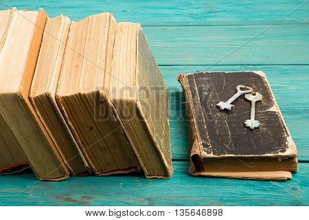 Old Keys On A Old Book And Stack Of Antique Books On Blue Wooden Desk