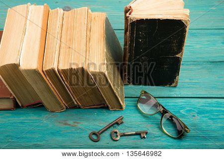 Old Keys, Glasses And Stack Of Antique Books On Blue Wooden Desk