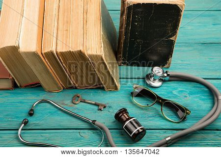 Old Medical Books With Stethoscope, Glasses, Bottle And Key On Blue Wooden Desk