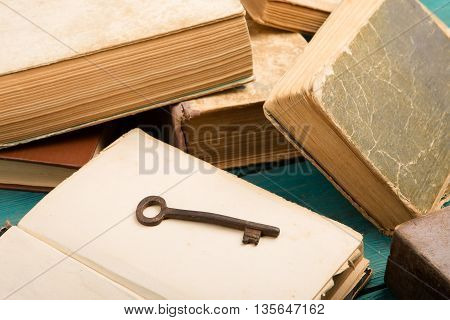 Old Key And Stack Of Antique Books