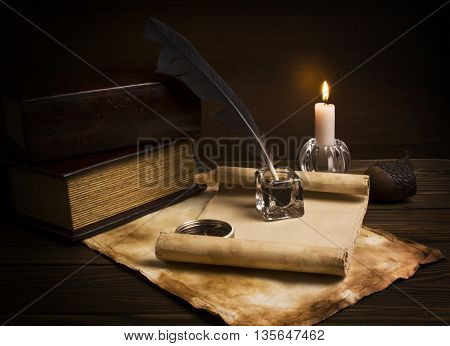 Old articles, book and candle on wooden table.