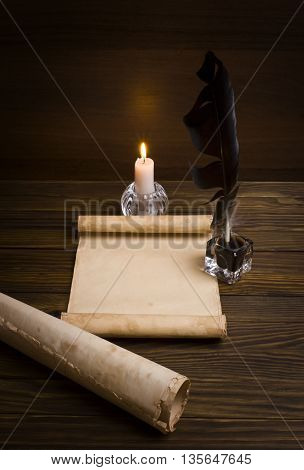 Old paper, candle and a feather on a wooden table.