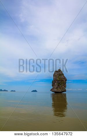 The haze of the warm sea - background for the huge stone cliff. Island
