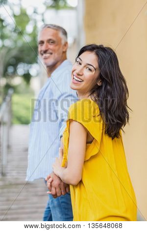 Portrait of happy woman holding mans hand while strolling in city