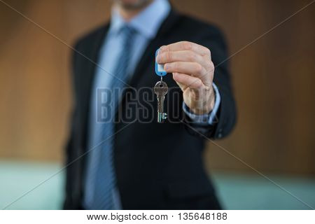 Real estate agent holding key of resort