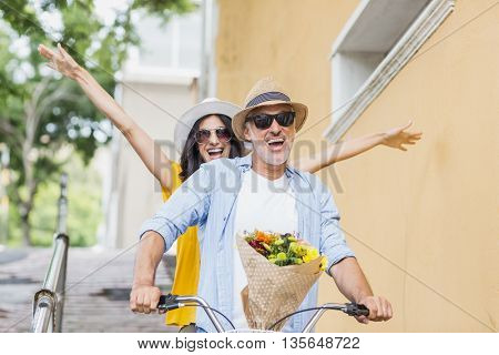 Front view of cheerful couple cycling in city