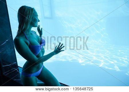 Woman in bikini touching a glass at resort