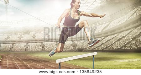 Athletic woman doing show jumping against view of a stadium