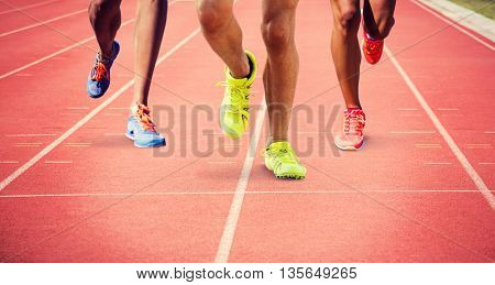Close up of sportsman legs running against focus of athletics track
