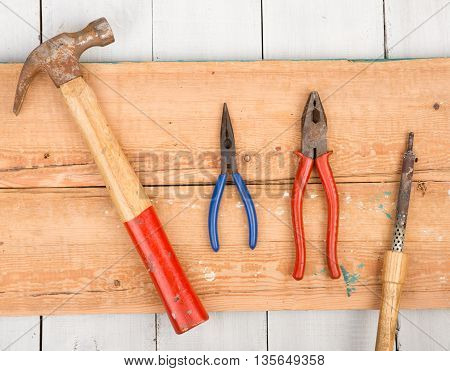 Set Of Old Tools - Hammer, Pliers And Soldering Iron On Wooden Background