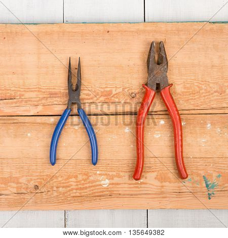 Set of old tools - old pliers on wooden background