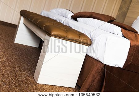 Brown upholstered leather footstool at the end of a luxury bed in a close up tilted angle view