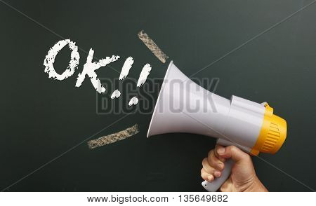 megaphone in front chalkboard with text ok