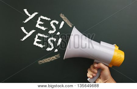 megaphone in front chalkboard with text yes