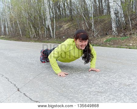 Young Woman Pushups Outdoors In Nature.