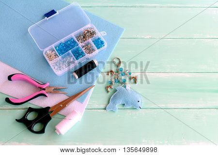 Cute felt Dolphin keyring with beads. Blue felt sea animal keychain. Materials and tools set to create crafts. Summer kids creativity. Child workplace. Blue wooden background with empty space for text