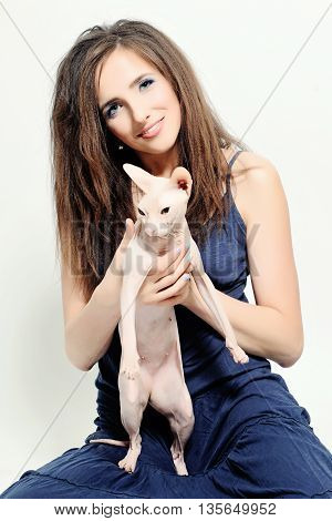 Woman holding Hairless Sphynx Cat on white