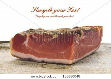 A piece of Parma ham with rosemary close up on wooden background